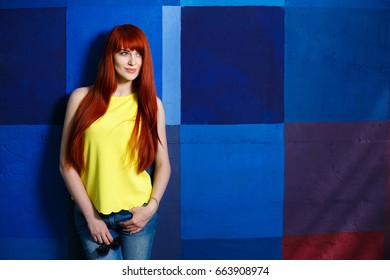 Youth, city style, women fashion, outerwear, jeans wear. Young stylish slim girl with long red hair standing on bright background