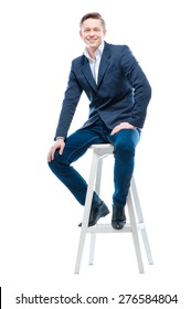 Youth and confidence. Attractive young man sitting on chair. Isolated on white.