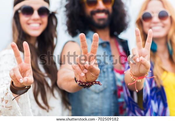 Jugendkultur, Geste und Konzept der Menschen - Lächelnde junge Hippie-Freunde in Sonnenbrillen, die auf der Hand des Friedens im Freien zeigen