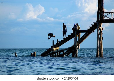 Youth diving from a pier on Prison Island in Indian Ocean