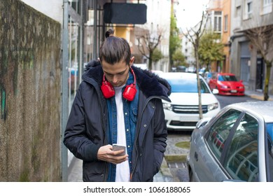 youth with earphones walking down the street with mobile phone