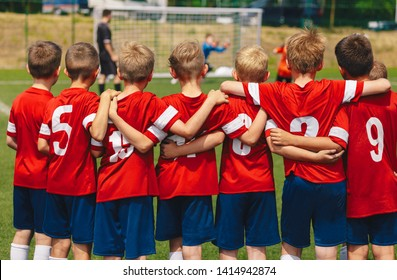Youth european football team in red shirts. Young boys of soccer club on the stadium during final competition. Kids soccer team in huddle on field. Soccer penalty shootout