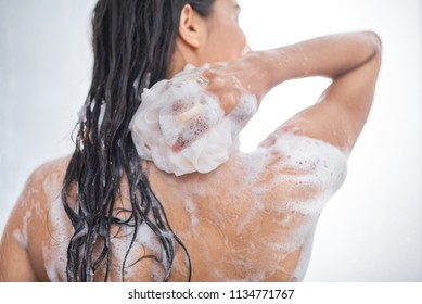 Youth female with wet hair washing body while holding fluffy sponge in hand. Hygiene concept