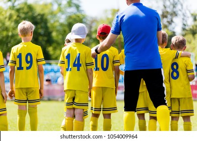 Youth football coach talking to childrens soccer team. Young football players with coach. Soccer coach coaching from the bench.