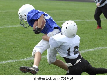 Youth football player tackles another.