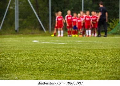 Youth Football Team with Coach on Pitch; Blurred Soccer Background. Soccer Training Session for Kids; Young Football Players Listening Coach Before the Training Match.