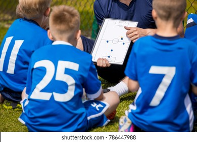 Youth Football Team with Coach at the Soccer Stadium. Boys Listening to Coach's Instructions Before Competition. Coach Giving Team Talk Using Soccer Tactics Board