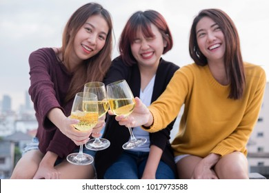 Youth friendship party concept. Group of asian friends drinking and having fun outdoor cheering at top roof.