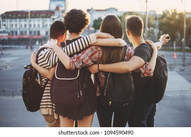 Youth, friendship, togetherness, happiness, adventure, freedom. Group of friends standing together hugging at city background
