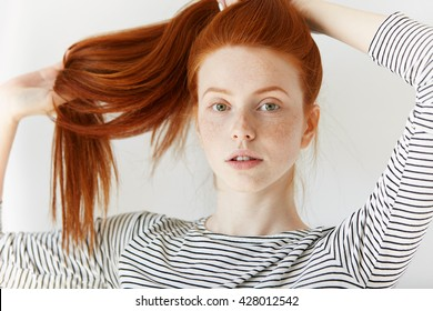 Youth and happiness concept. Close up view of beautiful Caucasian teenage girl in sailor shirt, looking at the camera, playing with her long ginger hair. Young woman with perfect healthy freckled skin