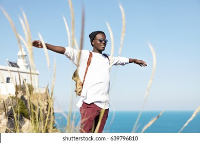 Youth, happiness, freedom and travelling. Absolutely happy and carefree dark-skinned tourist outstretching or spreading his arms feeling good vibes, looking positive, against blue ocean background