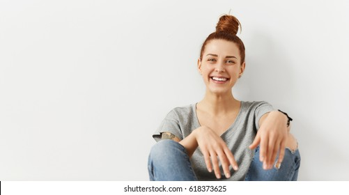 Youth and happiness. Style and clothing. Beautiful red-haired hipster girl with hair knot relaxing at home, leaning on white wall, looking at camera with happy smile, enjoying leisure time indoors