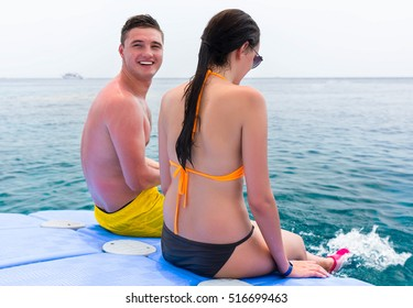 Youth laughing while sitting on pontoon in front of the beautiful and clean sea after swimming