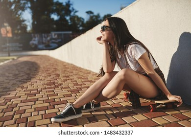 Youth, leisure and outdoor activity concept. Cheerful dreamy hipster skater girl sit on wooden penny board near white wall watching summer sunset, smiling delighted, learn how perform kickflip