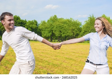 Youth Lifestyle: Caucasian Couple Relaxing Outdoors. Man Dragging Her Lady by Hands.  Holiday and Vacation Concepts. Horizontal Image Composition