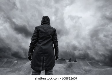 Youth lifestyle concept, unrecognizable hooded person standing in empty futuristic skateboarding park, dramatic sky in background for uncertain and unpredictable future