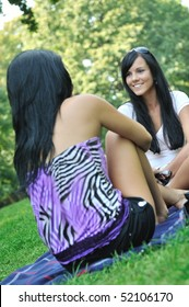 Youth lifestyle - conversation of two young friends (girls) siting on rug laid in grass outdoors  (park).