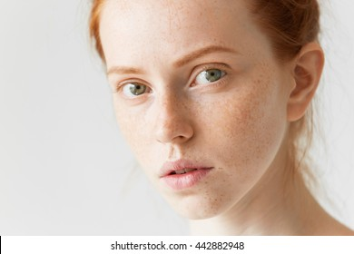 Youth and skin care concept. Highly-detailed close up portrait of pretty teenage girl with perfect clean freckled skin and green eyes looking at the camera with calm face expression, with lips parted