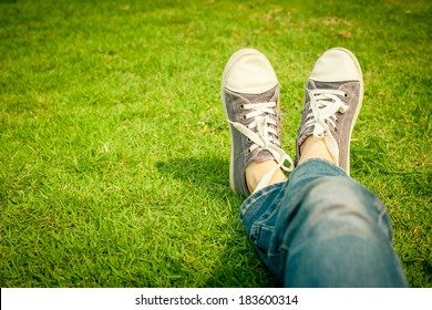 youth sneakers on girl legs on grass during sunny serene summer day.