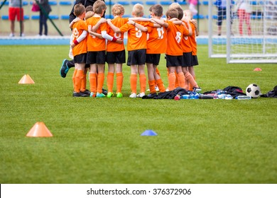 Youth soccer football team. Group photo. Soccer players standing together united. Soccer team huddle. Teamwork, team spirit and teammate example.