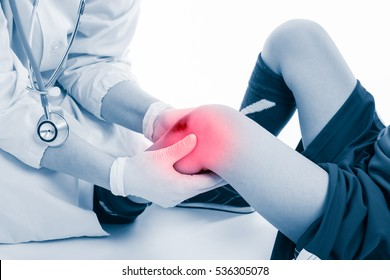 Youth soccer player knee pain, on white background. Doctor checking and give first aid at knee patient. Photo with color increase blue skin and red spot indicating location of pain.