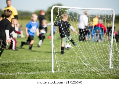 Youth Soccer - This is a shot of a youth soccer team and their coaches playing a game. Shot with a shallow depth of field with the focus set on the goal.