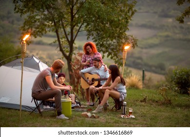 Youth socializing with guitar in front of tent at night fall in camp