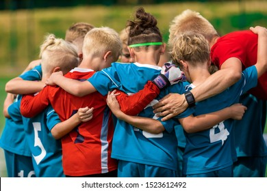 Youth sports coach witch children on soccer field. Kids huddling before the final tournament match. Kids bending down in huddle