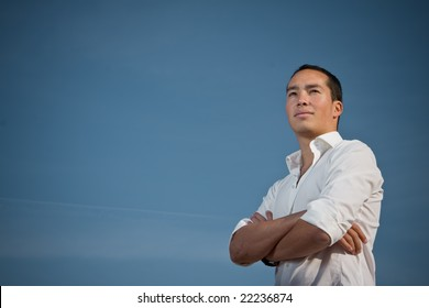 Youth standing with arms folded against blue sky looking forward