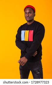 Youth street fashion concept - Portrait of confident sexy black man in stylish sweatshirt on yellow background.