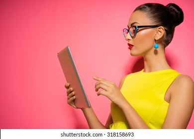 Youth and technology. Colorful studio portrait of young attractive brunette woman using tablet computer against pink wall.