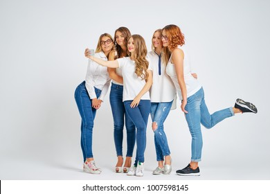 Youth and technology. Full length studio portrait of five beautiful young women laughing and taking selfie on smartphone together.