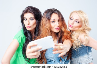 Youth and technology. Three beautiful young women laughing and taking selfie on smartphone together. Isolated on white.