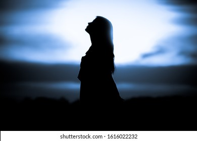 Youth woman soul at blue sun meditation dreaming past times. Silhouette in front of sunset or sunrise in summer nature. Symbol for healing burnout therapy, wellness relaxation or resurrection