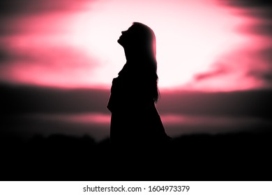 Youth woman soul at red sun meditation dreaming past times. Silhouette in front of sunset or sunrise in summer nature. Symbol for healing burnout therapy, wellness relaxation or resurrection