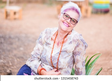 Youthful aged senior lady caucasian woman with pink and white hair smile at the camera - diversity and alternative concept for mature people like life with no limit age - beautiful retired woman