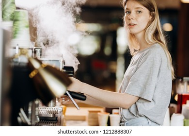 A youthful blonde slim gir,dressed in casual outfit,cleans the coffee machine with steam in a modern coffee shop.