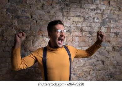 Youthful exited male standing against brick wall
