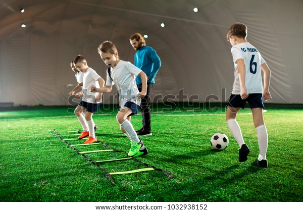 Youthful kids in uniform exercising during football training on green lawn