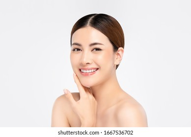 Youthful pretty Asian woman with hand touching face on white background for beauty and skin care concepts
