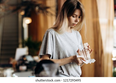A youthful pretty blonde girl,dressed in casual style, holds a clean glass and looks at it in a modern coffee shop.