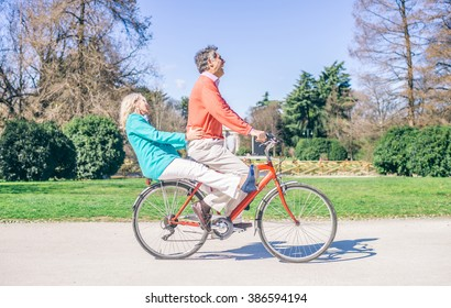 Youthful senior couple riding on a bicycle in a park - Two pensioners having fun and acting like young people