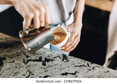 A youthful slim kind blonde girl,dressed in casual outfit,skillfully adds milk to coffee in a modern coffee shop.
