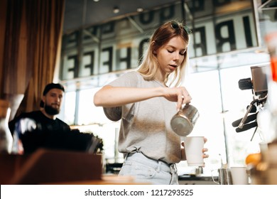 A youthful thin blonde girl,wearing casual cothes,is shown adding milk to the coffee in a cozy coffee shop.