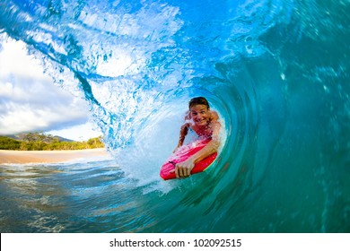 Youthful young man Boogie Boarding Blue Wave