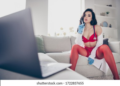 You've been bad boy. Photo of hot lady work home sit couch spread legs online notebook chat undress play sensual naughty nurse role hold syringe take off lab coat look screen webcam red bikini indoors