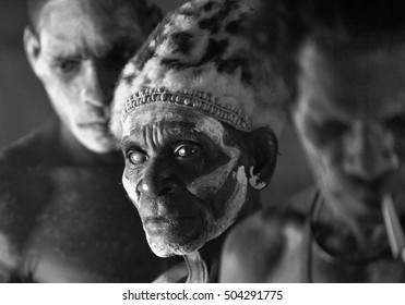 YOUW VILLAGE, ATSY DISTRICT, ASMAT REGION, IRIAN JAYA, NEW GUINEA, INDONESIA - MAY 23, 2016: Black and white portrait of a man from the tribe of Asmat people. Traditional face painting. New Guinea.