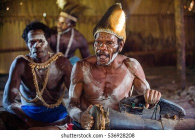 YOUW VILLAGE, ATSY DISTRICT, ASMAT REGION, IRIAN JAYA, NEW GUINEA, INDONESIA - MAY 23, 2016: Man with a drum in the house. Man from the tribe of Asmat with traditional face painting beats the drum