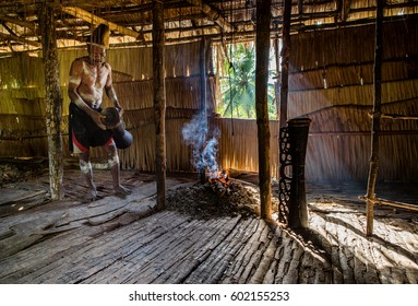 YOUW VILLAGE, ATSY DISTRICT, ASMAT REGION, IRIAN JAYA, NEW GUINEA, INDONESIA - MAY 23, 2016: Man from the Asmat tribe with ritual face painting. Welcoming ceremony in traditional asmat men house Jeu