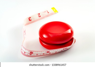 Yo-yo dieting, yo yo effect or weight cycling concept theme with a yoyo toy wrapped in tape measure or measuring tape symbolizing the fluctuating of a unsuccessful diet, isolated on white background